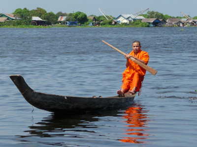 moine sur une barque près des villages flottants
